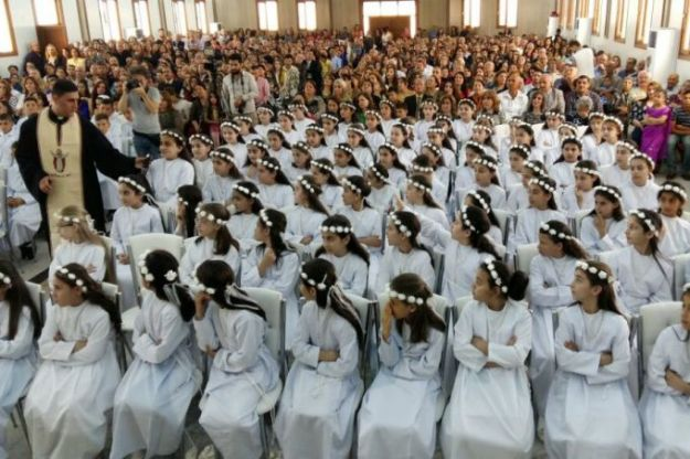 Iraqi refugee children make First Communion in Erbil camp. Photo by Deacon Roni Momica, from the article.